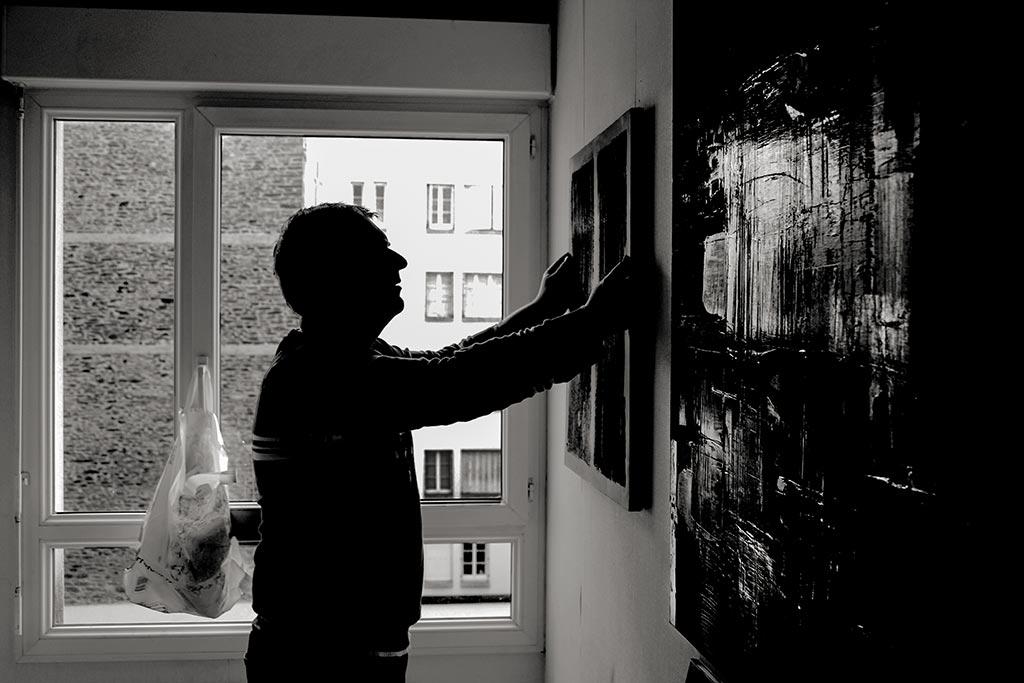peintre accrochant une toile